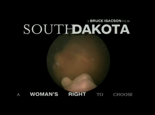 A still shot from the trailer of the film. The background is black. In the middle there is a circle featuring an in utero fetus in a very late gestational period. The fetus's eye, nose, and hand are visible. The text above reads 'A Bruce Isacson film. South Dakota' the text below the fetus reads 'a woman's right to choose' in smaller letters.