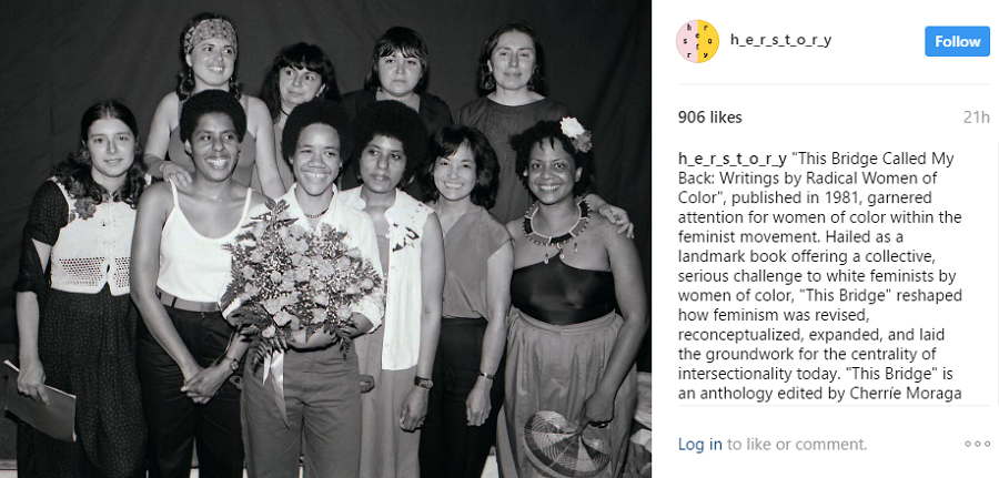 A black-and-white photo of group of women of color posing, with one in the middle holding a bouquet of roses