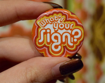 """a woman's hand holding a colorful pin that reads """"What's Your Sign?"""""""