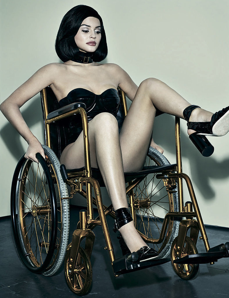 Kylie Jenner seated in a golden wheelchair in Interview magazine. She is wearing a black choker and black bustier with black high heels and is raising one leg.