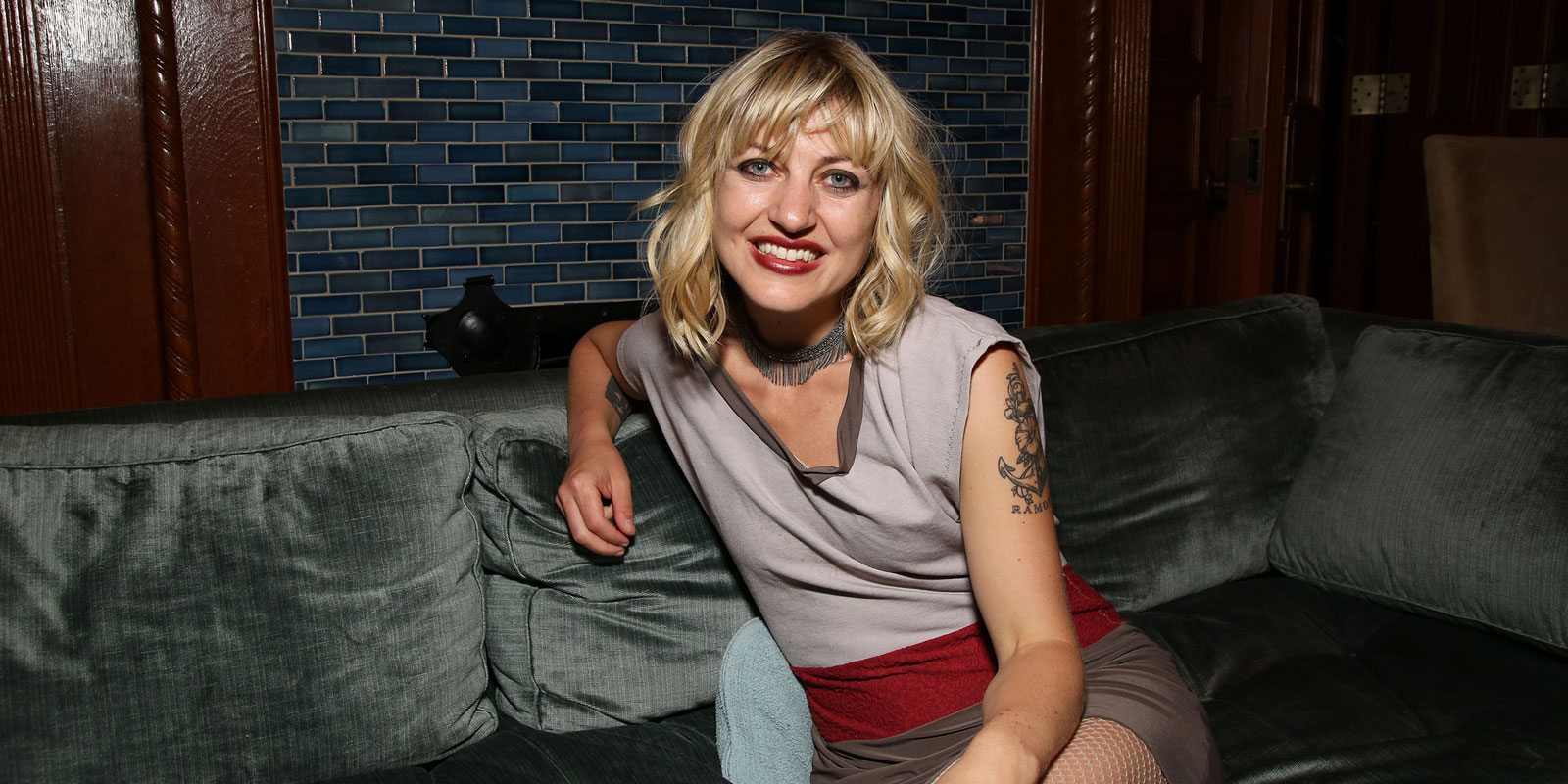 a white woman with short, blond hair and red lipstick sits on a couch