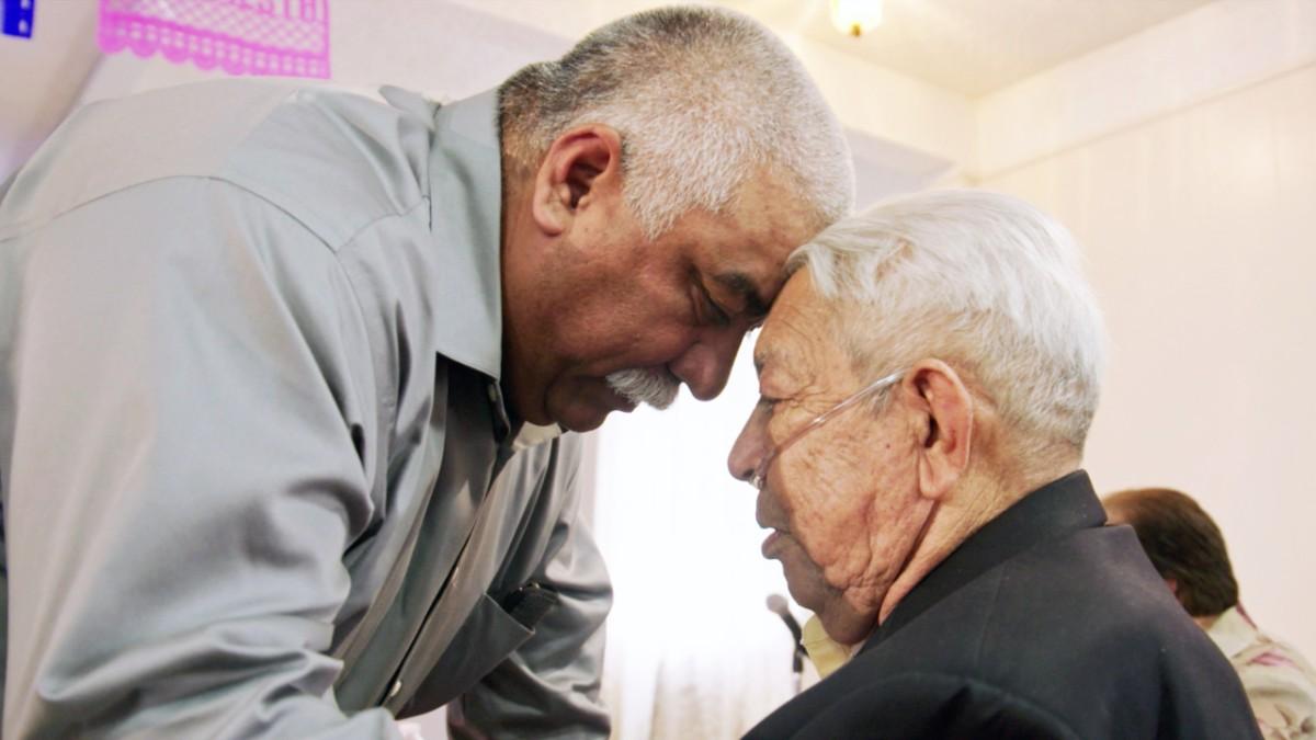 two Latinx men, one wearing oxygen, embrace in HBO's Alternate Endings documentary