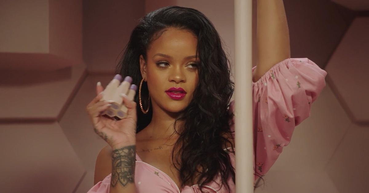 Rihanna wearing hot pink lipstick, big gold hoops, and a puffy pink dress while holding up her Fenty Match Stix