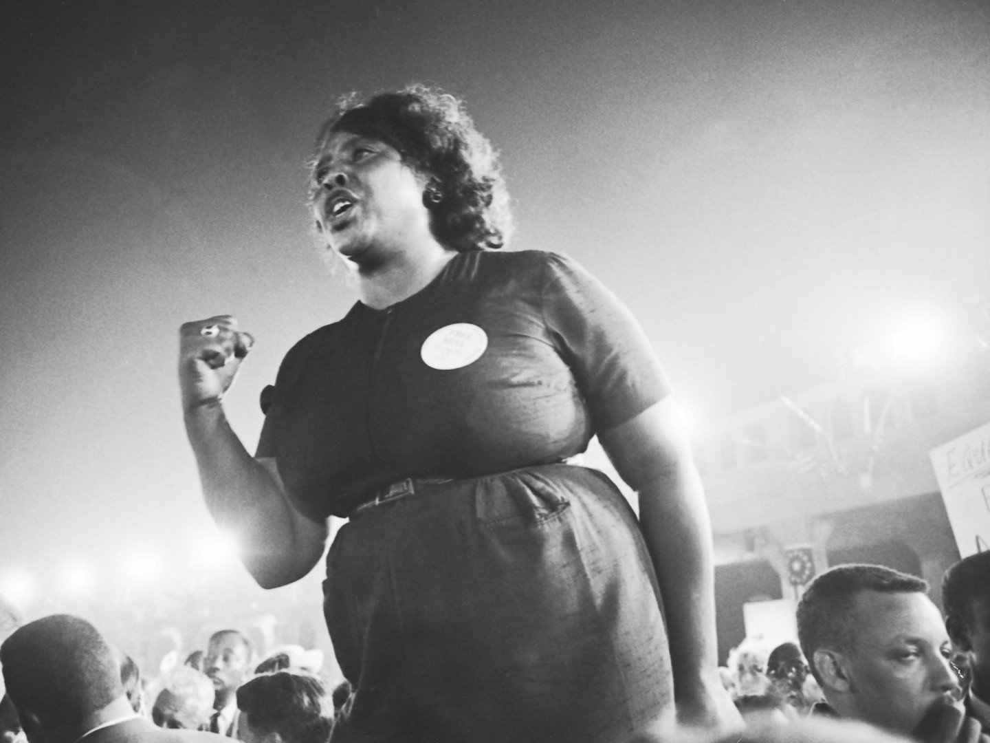 a photograph of a Black woman with short, black, hair leading a rally