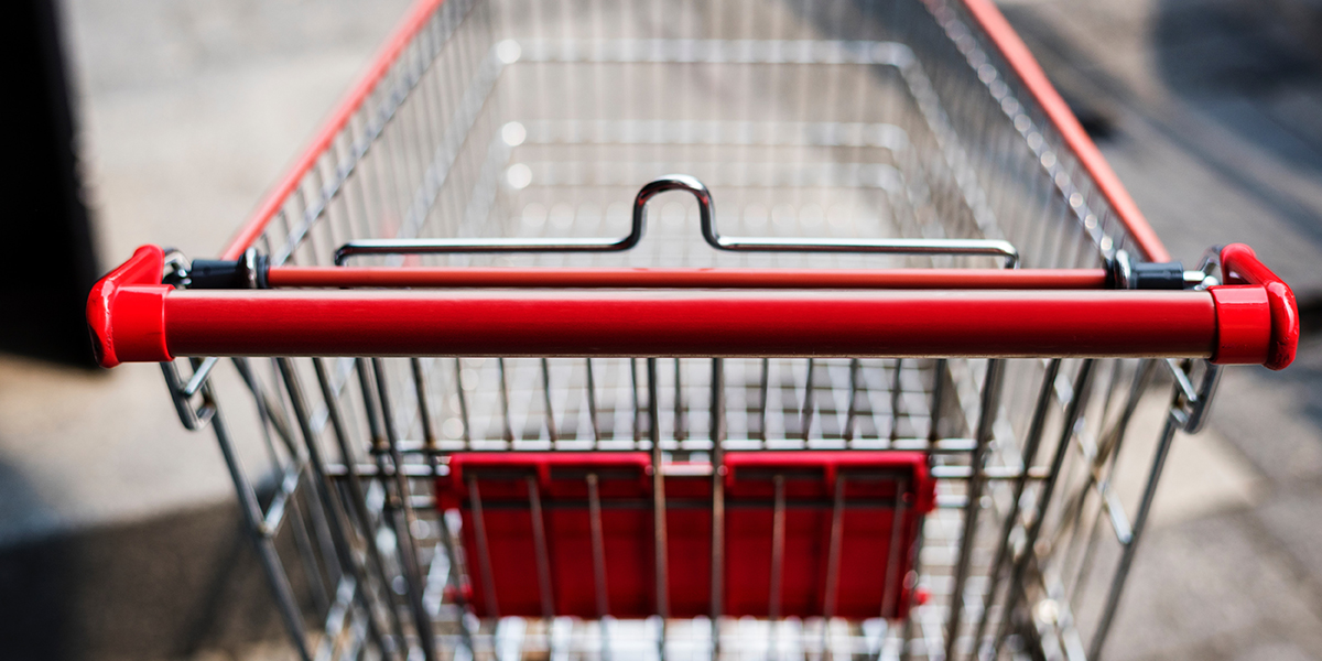 A shopping cart from the perspective of the person pushing it, the background is blurred