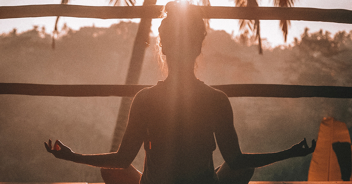 The silhouette of a person with their legs crossed in a yoga pose in a sunny tropical location