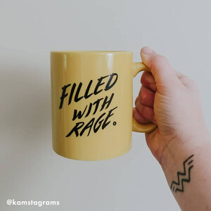 """photo of Rage member's hand holding up a yellow mug with the words """"Filled with Rage"""""""