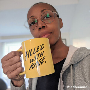 "photo of Rage member Jae Hermonn, a Black woman with shorn hair and wearing glasses, holding up a yellow mug with the words ""Filled With Rage"""
