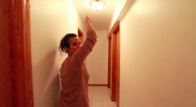 a young woman points to a fake smoke detector in her ceiling
