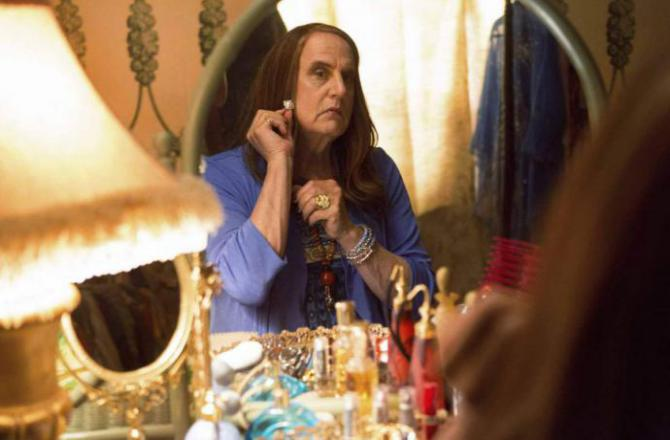 Jeffrey Tambor, playing Maura, puts on makeup in a mirror