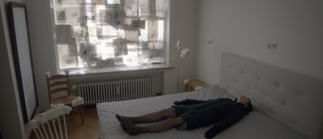 a still from Nymphomaniac, featuring Joe lying on her bed