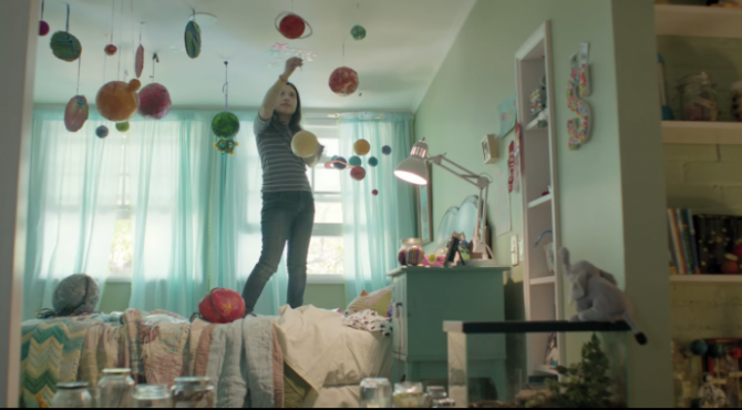 verizon ad still shows a girl hanging planets in her room