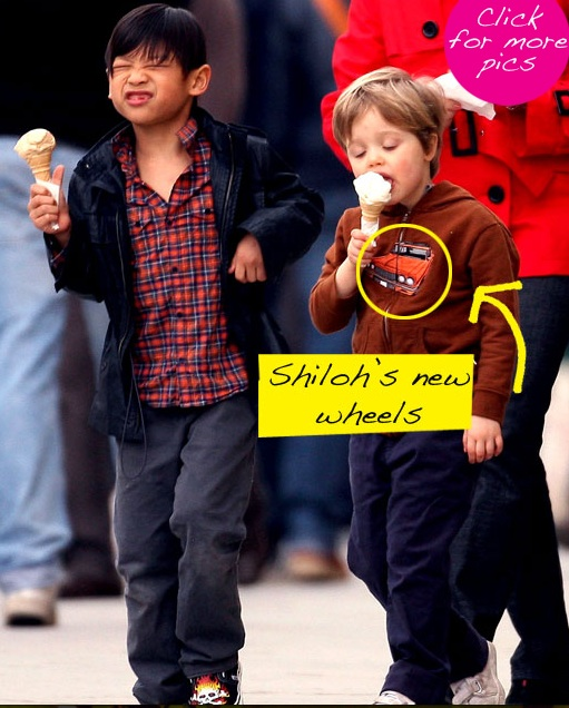 Shiloh and brother Pax eat ice cream while walking down the street. Shiloh is wearing a brown sweatshirt with a truck on it. A tabloid-style bubble points to the truck and says Shiloh's New Wheels