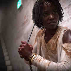 Lupita Nyong'o as Adelaide Wilson in Us, wearing a muddy, ripped top, handcuffed while holding a weapon and looking frightened.