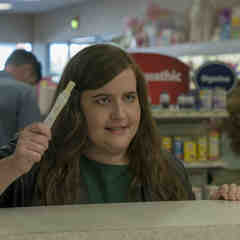 Annie (Aidy Bryant) at a pharmacy counter holding a positive pregnancy test