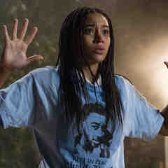 a lightskinned Black person with long braids is wearing a light-blue shirt that says Rest in Peace Khalil and has her hands up
