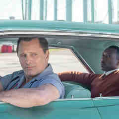 Viggo Mortensen leans out the window of a turquoise Cadillac while Mahershala Ali sits in back