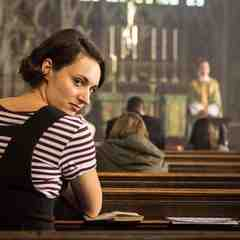 a white woman with short, brown hair looks over her shoulder while sitting in a church pew