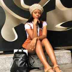 Nandi Howard, a thin Black woman wearing a leopard print fuzzy hat, sits on a concrete stoop