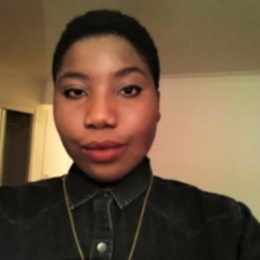 Adwoa Afful, a Black person with short black hair, smirks at the camera