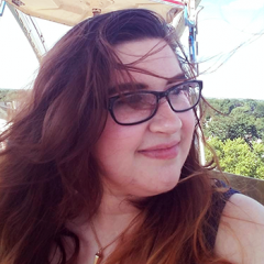 A person with fair skin, brown hair, and glasses looking to the right while on a Ferris wheel.