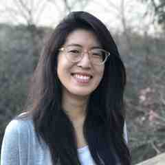 Hannah Amaris Roh, a Korean American writer with glasses, smiles at the camera