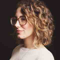 Melissa A. Fabello, a white woman with short, blond, curly hair, poses in profile