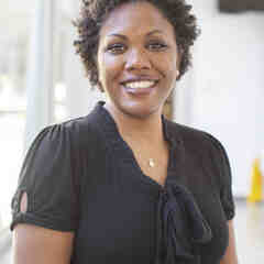 Joshunda Sanders, a Black woman with short black hair, smiles brightly at the camera
