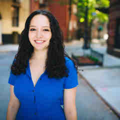 Meghan Racklin, a white writer, smiles at the camera while wearing a blue blouse