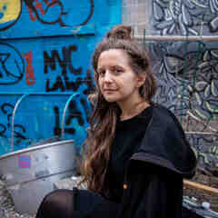 Liz Pelly, a white woman with brown hair in a bun, sits in front of a graffitied wall