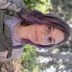 A white person with shoulder length lavender hair looks directly at the camera. She is wearing dark green coveralls that match her eyes, with tattoos reaching down her arms, and pine trees and ferns are in the background out of focus.