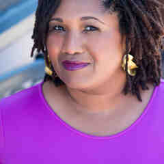 Tamara Winfrey-Harris, a plus-size Black woman with short brown locs, poses in purple lipstick and a purple shirt with gold hoop earrings