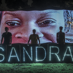three white people stand in front of a photo of Sandra Bland with lit up signs that bare her name