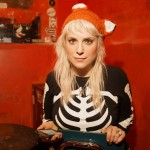 Blonde woman in hat with ears and skeleton sweater holds a smartphone