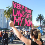 a white person with a blonde and black mullet holds a Keep Your Laws Off My Body sign at a protest