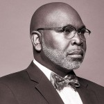 A darkskinned man with black glasses and a neat salt-and-pepper beard in a suit and purple bow tie gazes to the right of the frame