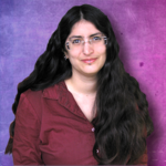 Shiri Eisner, an Israel genderqueer writer, with long, Black hair and glasses