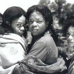 three Black women holding each other while staring at the camera