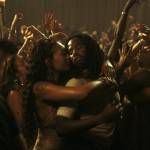 a brown couple dance, facing each other, in a crowd of revelers