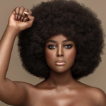 Dark-skinned black woman in afro faces forward with fist raised