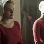 Elisabeth Moss plays Offred, a white woman dressed in a white and red bonnet, in The Handmaid's Tale