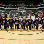 The Indiana Fever, a WNBA team, kneel together, their arms linked, on the basketball court together in black uniforms