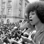 Angela Davis, a lightskinned Black woman with an afro, speaks into a microphone at a rally