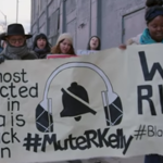 "Protesters marching and holding a giant sign that says, ""The most unprotected person in America is the Black Woman. Still we rise. #MuteRKelly #BlackGirlsMatter"""