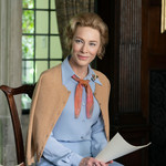 Cate Blanchett plays Phyllis Schlafly, a white woman with short, blond hair, wearing a purple shirt and sitting down