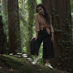 Aditi Mayer, a brown-skinned woman with long black hair, poses in a forest in a linen suit