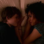 Two teen girls, one white with short brown hair and one Black with shoulder-length curly brown hair lay in bed next to each other, their noses nearly touching as they smile.