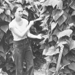 a white woman stands in front of a wall of foliage