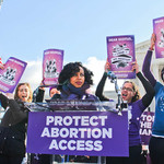 a Latinx woman wearing a scarf stands on a podium behind a Protect Abortion Access sign