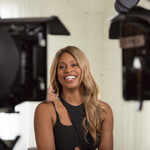 Laverne Cox, a Black trans woman with blond hair, smiles at the cameras in Disclosure.